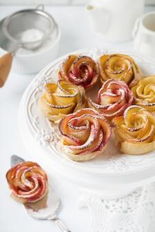 Pyszne ciasta z różą jabłkową w ceramicznej formie na jasnym betonowym lub kamiennym tle.