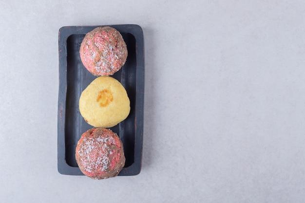 Pyszne ciasteczka na desce na marmurowym stole