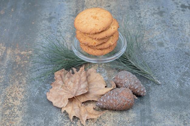 Pyszne ciasteczka w szklanym słoju z liśćmi i szyszkami na marmurowym tle. wysokiej jakości zdjęcie