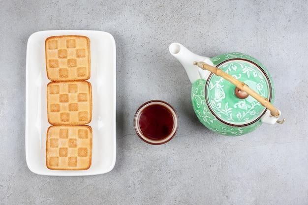 Pyszne ciasteczka z filiżanką herbaty i czajniczkiem. wysokiej jakości zdjęcie