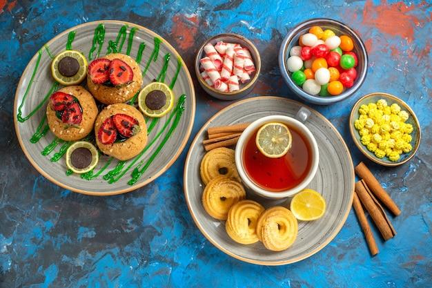 Pyszne ciasteczka z widokiem z góry z filiżanką herbaty i cukierkami na niebieskim słodkim owocu?