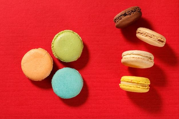 Pyszne ciastka makaroniki w innym kolorze na czerwonej teksturowanej powierzchni. widok z góry