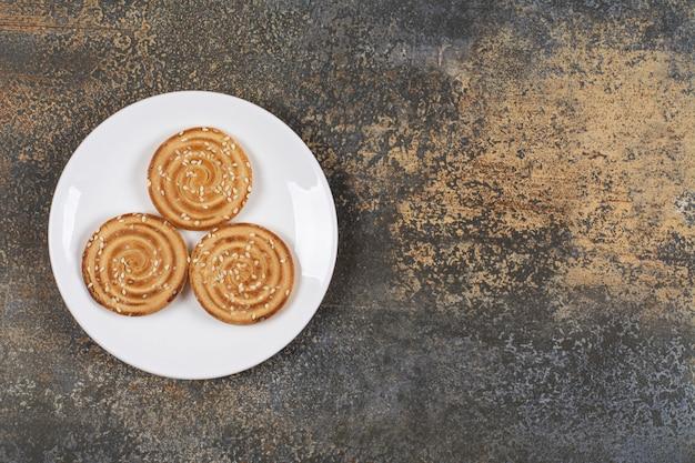 Pyszne ciastka sezamowe na białym talerzu.