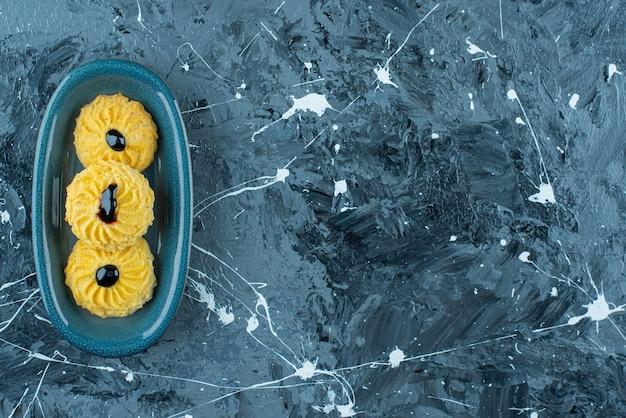 Pyszne ciastko na talerzu, na niebieskim stole.