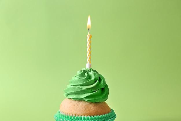 Pyszne ciastko urodzinowe z płonącą świeczką na kolorowym tle