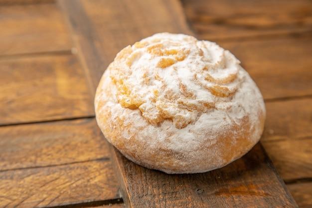 Pyszne ciastko z proszkiem kokosowym na podłoże drewniane