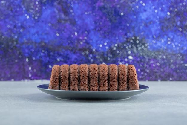 Pyszne ciasto czekoladowe na ciemnym talerzu.