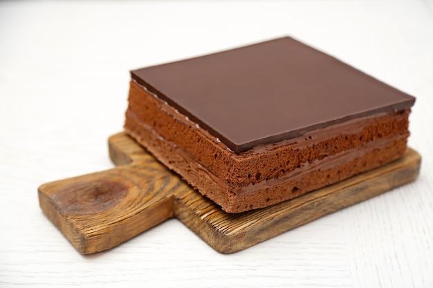 Pyszne ciasto czekoladowe na drewnianej desce do krojenia na białym tle