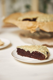 Pyszne ciasto czekoladowe z kremem na białym stole z estetycznymi detalami
