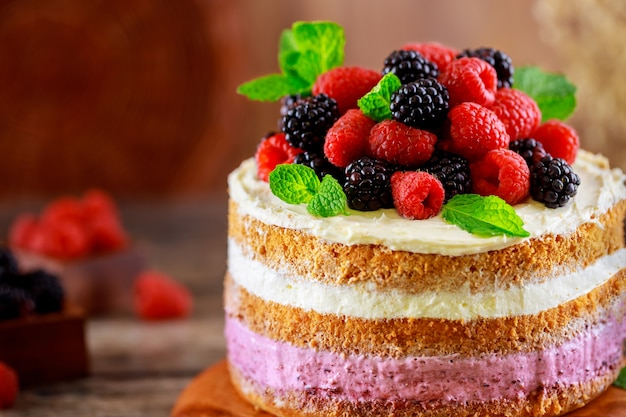 Pyszne ciasto jagodowe ozdobione świeżymi malinami i jeżynami na podłoże drewniane.