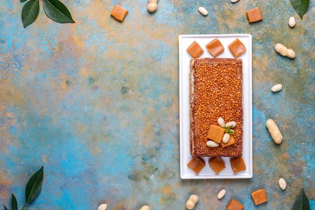 Pyszne ciasto karmelowo-orzechowe z orzeszkami ziemnymi i cukierkami karmelowymi, widok z góry