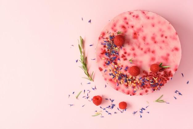 Pyszne ciasto malinowe ze świeżymi jagodami, rozmarynem i suchymi kwiatami. koncepcja wegetariańska, wegańska