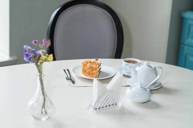 Pyszne ciasto marchewkowe i filiżanka czarnej herbaty na stole w przytulnej kawiarni