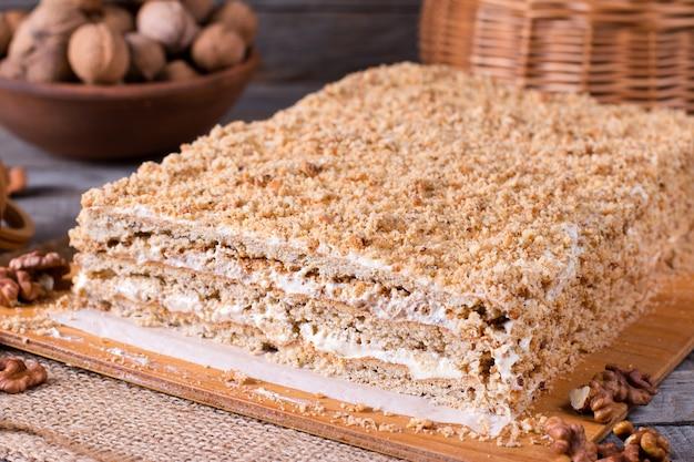 Pyszne ciasto miodowe ze śmietaną i orzechami na rustykalnym tle
