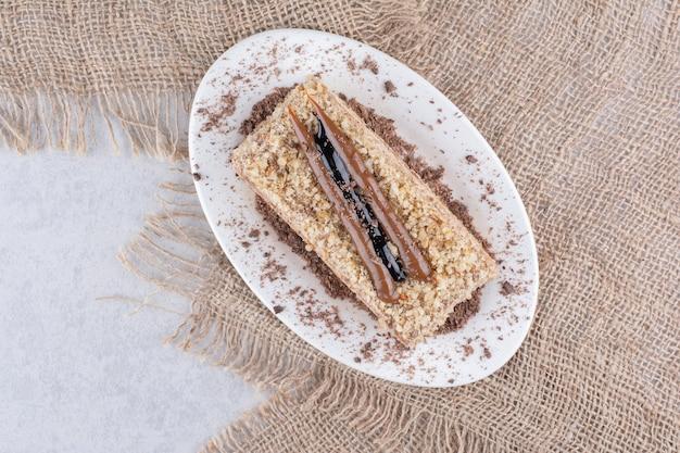 Pyszne ciasto na białym talerzu z jutą. zdjęcie wysokiej jakości
