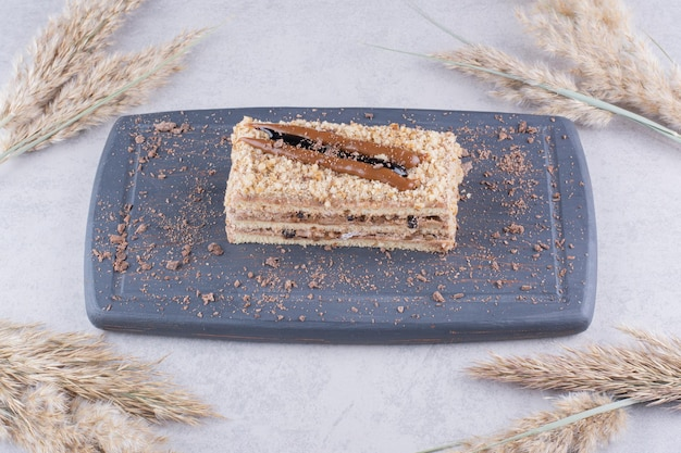 Pyszne ciasto na ciemnym talerzu z kłosami pszenicy.