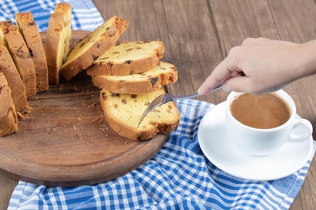 Pyszne ciasto na drewnianym talerzu z filiżanką kawy na boku