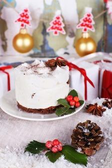 Pyszne ciasto na spodku z ostrokrzewem i jagodami na świątecznej dekoracji