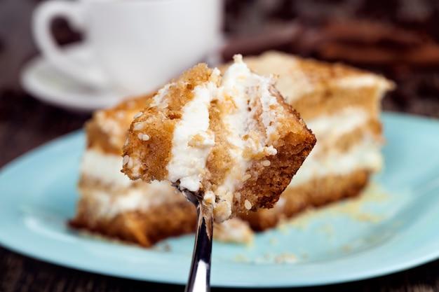 Pyszne ciasto pokrojone na kawałki, ciasto wielowarstwowe z kremem maślanym, deser z dużą ilością kalorii, zbliżenie ciasta