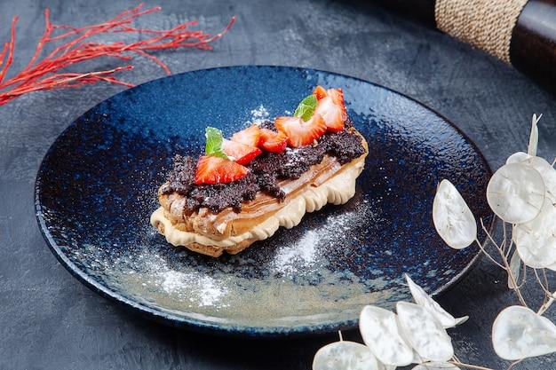Pyszne ciasto profiteroles z pastą truflową, budyniem i truskawkami na ciemnym talerzu. deser na lunch. piekarnia. zdjęcie żywności dla menu lub przepisu