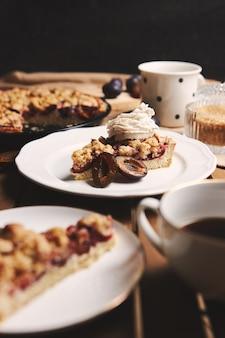 Pyszne ciasto śliwkowe z kawą chemex i dodatkami z tkaniny na drewnianym stole z tkaniny