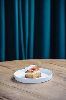 Pyszne ciasto truskawkowe z bitą śmietaną na drewnianym stole. mille feuille truskawek.