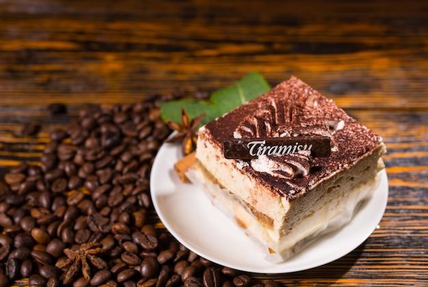 Pyszne ciasto w kształcie kwadratu kawałek w płycie otoczony ziaren kawy na ciemnym poplamionym tle drewnianych