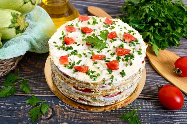 Pyszne ciasto z cukinii, pomidorów i sera na drewnianym stole. ciasto warzywne