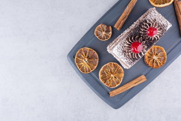 Pyszne ciasto z cynamonem i plastrami pomarańczy na ciemnym talerzu. zdjęcie wysokiej jakości