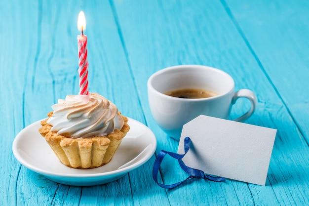 Pyszne ciasto z kremem i płonącą świecą kubek pachnącej kawy pusty kartkę z życzeniami na niebieskim drewnianym stole