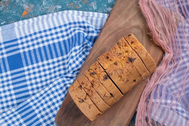 Pyszne ciasto z wieloma składnikami na drewnianej desce do krojenia