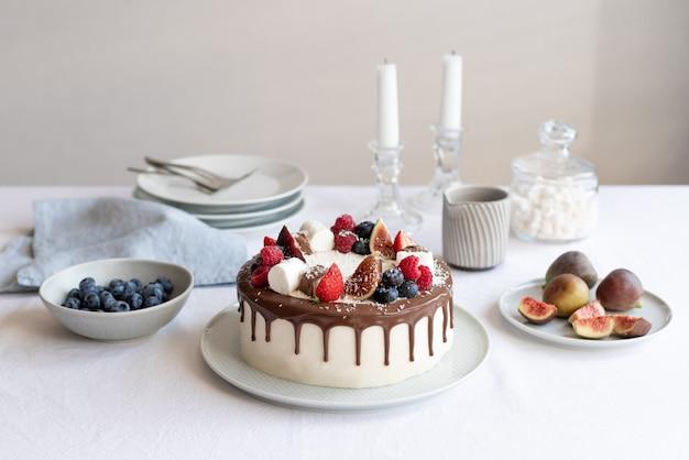 Pyszne ciasto ze świeżymi jagodami i czekoladą stół podany na urodzinową kolację w salonie