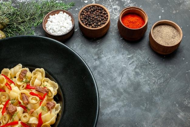 Pyszne conchiglie z warzywami i zieleniną na talerzu i nożem oraz różnymi przyprawami na szarym stole