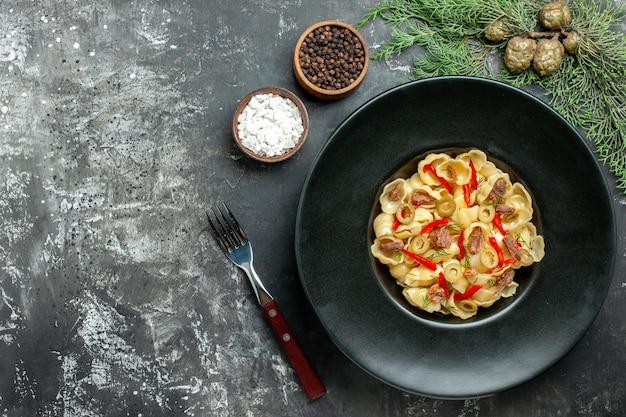 Pyszne conchiglie z warzywami i zieleniną na talerzu i nożem oraz różnymi przyprawami na szarym tle