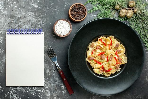 Pyszne conchiglie z warzywami i zieleniną na talerzu i nożem oraz różnymi przyprawami obok notatnika na szarym tle