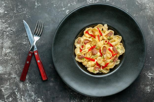 Pyszne conchiglie z warzywami na talerzu i nożem na szarym stole