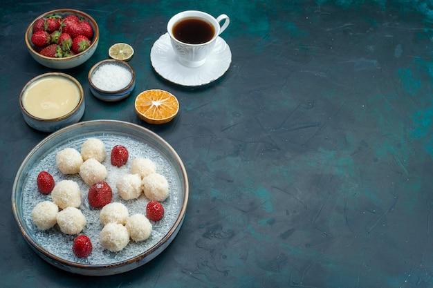 Pyszne cukierki kokosowe ze świeżymi czerwonymi truskawkami i filiżanką herbaty