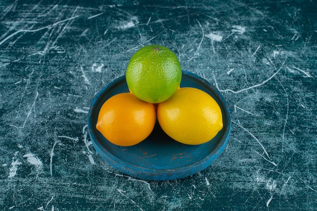 Pyszne cytryny na drewnianym talerzu, na marmurowym tle. zdjęcie wysokiej jakości