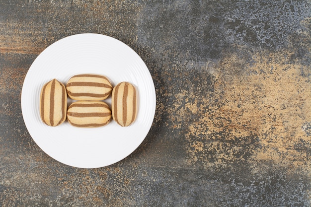 Pyszne czekoladowe herbatniki w paski na białym talerzu.