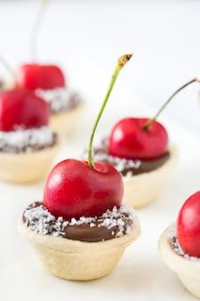 Pyszne czekoladowe tartaletki z jedną wiśnią i kokosem na białym tle