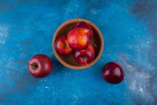 Pyszne czerwone jabłka błyszczące umieszczone na niebieskim stole.