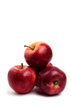 Pyszne czerwone jabłka na białym tle na białym stole.