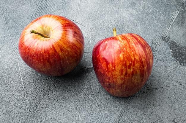 Pyszne czerwone jabłka ustawione, na szarym tle kamiennego stołu, z miejscem na tekst