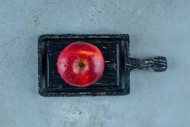 Pyszne czerwone jabłko na desce, na marmurowym tle. zdjęcie wysokiej jakości