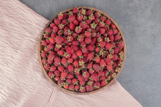 Pyszne czerwone maliny na drewnianym talerzu. zdjęcie wysokiej jakości