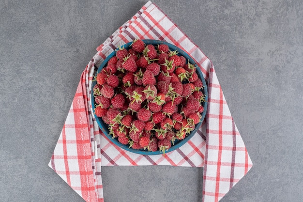 Pyszne czerwone maliny na niebieskim talerzu. zdjęcie wysokiej jakości