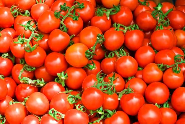 Pyszne czerwone pomidory. gospodarstwo rolne na rynku letnich tacek pełne ekologicznych warzyw może być używane jako.