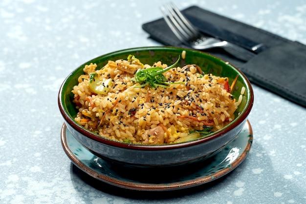 Pyszne danie panazjatyckie - ryż z woka z kurczakiem, warzywami i sosem słodko-kwaśnym w zielonej misce na szarej powierzchni. zbliżenie, selektywne skupienie
