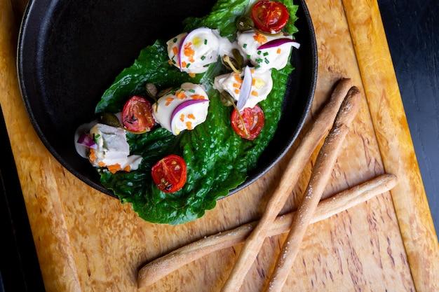 Pyszne danie w restauracji vitello tonato w restauracji. zdrowe ekskluzywne jedzenie na dużym czarnym talerzu zbliżenie