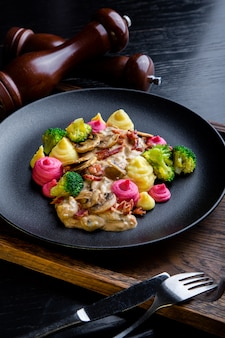 Pyszne danie z wołowiny strogans w restauracji. zdrowe ekskluzywne jedzenie na dużym czarnym talerzu zbliżenie